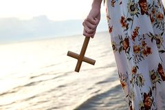 Christian lady girl holding a holy cross in her hand and standing on the beach during sunset evening time. stock photos