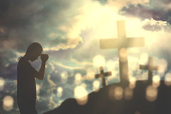 Christian man praying with folded palms. Silhouette of a young Christian man praying to god and folding palms with three crucifixes at sunrise stock photos