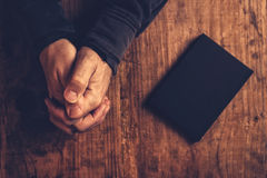 Christian man praying with hands crossed. And Holy Bible by his side on wooden desk in church, top view Stock Image
