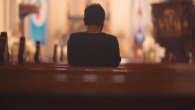 Christian man praying to GOD in church. Back view of Christian man praying to GOD while sitting on the bench in the church. Shot in 4k resolution stock video