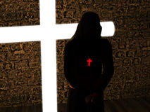 Christian monk with his head bowed, meditating. A stoned cross exists at background - 3D rendering Stock Photos