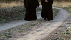 Christian monks walking on a country road stock footage