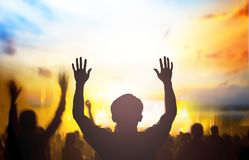 Christian music concert with raised hand. Devout followers raised their hands over sunset background stock photography
