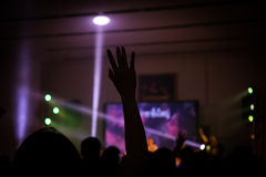 Christian music concert with raised hand. Indoor light stock photos