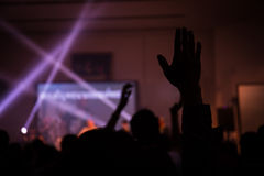 Christian music concert with raised hand. Indoor light royalty free stock photo