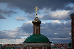 Christian Orthodox Cross. Photo of a Christian Orthodox cross towering over the city against a background of clouds Stock Photos