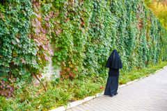 Christian Orthodox nun walking on street. Christian Orthodox nun walking near gape brick wall after exit from Church Royalty Free Stock Photo