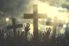 Christian people hands praying. Group of christian people hands praying together with three cross symbol and bright sunbeam on the sky stock images