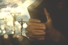 Christian person with bible. Picture of christian person holding a bible with crucifixion sign on the background royalty free stock image