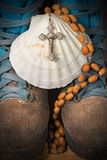 Christian Pilgrimage Symbols - Boots and Shell. Scallop shell with a wooden rosary beads with a silver crucifix over a pair of hiking boots. Symbols of the Royalty Free Stock Photo