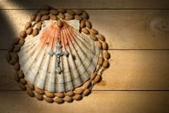 Christian Pilgrimage Symbols. Scallop seashell and wooden rosary beads with a silver crucifix on a wooden background. Symbols of Christian pilgrimage Royalty Free Stock Photo