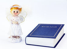 Christian post. Little angel girl with fluffy wings and the Bible Royalty Free Stock Photos
