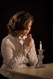 Christian Prayer with Cross. Woman holds wooden cross in hands while praying in front of candle Royalty Free Stock Photography