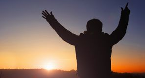 Christian prayer stand worship God in easter day concept vision to success financial. Soft focus and Silhouettes of man raise hand up worship God against blurred Stock Photos