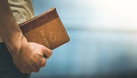 Christian preacher: Young man is holding the bible, praying. Young preacher is holding the holy bible, praying religion bibel religious catholic church faith god stock photography