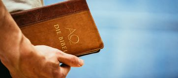Christian preacher: Young man is holding the bible, praying. Young preacher is holding the holy bible, praying religion bibel religious catholic church faith god royalty free stock photography