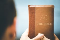 Christian preacher: Young man is holding the bible, praying. Young preacher is holding the holy bible, praying religion bibel religious catholic church faith god royalty free stock images