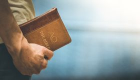 Christian preacher: Young man is holding the bible, praying. Young preacher is holding the holy bible, praying religion bibel religious catholic church faith god stock images
