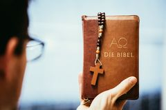 Christian preacher: Young man is holding the bible, praying. Young preacher is holding the holy bible, praying religion bibel religious catholic church faith god royalty free stock image