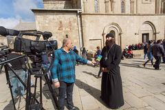 Christian priest gives a television interview near the Svetitskhoveli Cathedral, built in 4th century Royalty Free Stock Photography