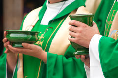 Christian priests holding bowls of wafer and wine. Christian priests holding bowls with wafer and wine during sacrament royalty free stock image