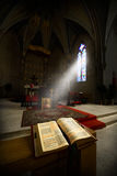 Christian Religion, Bible, Church, Jesus. The sun shines a beam through a stained class window. An open Bible rests with the word of God of the Christian Stock Images