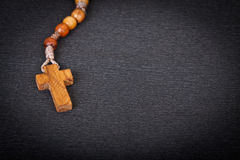 Christian Rosary. Close up of wooden cross of Christian Wooden Rosary on grey background Royalty Free Stock Photography