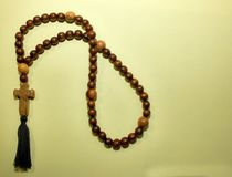 Christian rosary, beads. paternoster, with a wooden cross. Shiny brown stock image