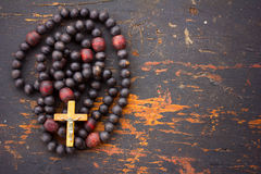 Christian rosary prayer with a cross on old black wooden background Stock Photography