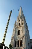 Christian Steeple and Hindu Flag Staff with Birds. A Catholic cathedral steeple along with a Hindu flag staff against a blue sky with birds flying between stock photo