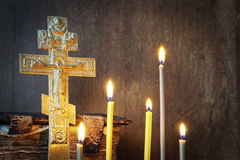 Christian still life with old metal cross and burning candles Royalty Free Stock Image