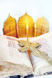 Christian still life with open ancient Bible and metal cross. Orthodox Christian still life with an open ancient Bible and metal cross on light background royalty free stock photography