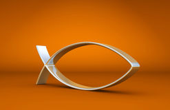 Christian symbol. A shiny metallic object in the shape of a fish which was an early symbol of Christianity on an orange background Stock Image