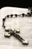 Christian symbols. Rosary with crucifix lying on open Bible Royalty Free Stock Photography