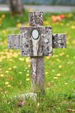 Christian tomb with stone cross and burial in a green meadow Stock Photos