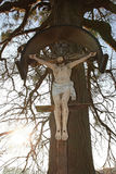 Christian wayside cross with jesus statue Stock Photo