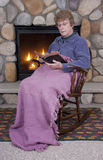 Christian Woman Bible Fireplace Rocking Chair. Mature senior Christian woman rests in her wooden rocking chair by the fireplace while reading her Bible. She is Royalty Free Stock Photography
