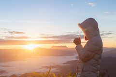 Christian woman hands praying to god on the mountain background with morning sunrise. Woman Pray for god blessing to wishing have stock photography