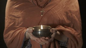 Christian woman holding tibetian singing bowl with candle stock footage
