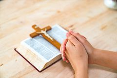 Christian woman praying with hands crossed and Holy Bible by his. Side on wooden desk in church, top view stock photos
