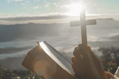 Christian woman praying on the mountain with morning sunrise. Hands crossed and Holy Bible . Background.  stock photos