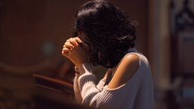 Christian woman praying to GOD in the church. Christian woman praying to GOD while sitting in the church with clasped hands. Shot in 4k resolution stock video footage