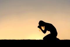 Christian Woman Sitting Down nella siluetta di preghiera Fotografie Stock Libere da Diritti