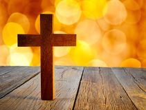 Christian wood cross on blur flare lights. And wooden background stock photo