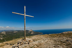 Christian wooden cross on mountain top, rocky summit, beautiful inspirational landscape with ocean, clouds and blue sky Stock Photo
