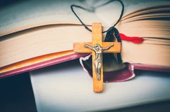 Christian wooden cross necklace on holy Bible. Religious concept - retro style royalty free stock photos