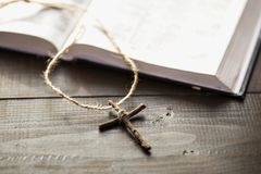 Cross next pages of the open Bible. Christian wooden cross next the open Holy Bible. The way to the God through prayer. Cross next the pages of the book stock images