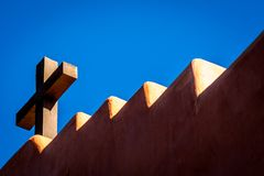 Christian cross on top of adobe church. Christian wooden cross on top of stepped roof of an adobe church royalty free stock images