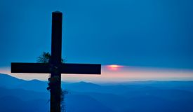 Christian worship cross overlooking mountains at sunrise. Christian worship cross overlooking mountains  at sunrise Royalty Free Stock Images