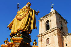 Christianity. Golden statue of a saint posing againt church tower Royalty Free Stock Image